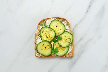 Healthy vegetarian sandwich with vegetables - cucumber. Cream cheese and microgreens