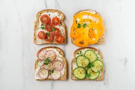 Healthy vegetarian sandwiches with vegetables - yellow pepper, tomato, cucumber and radish. Cream cheese and microgreens Standard-Bild