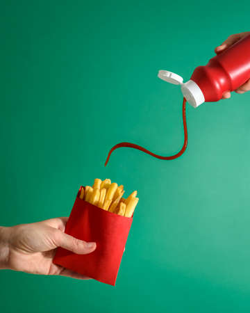 Fries potatoes in red package in hand on green background with tomato ketchup pouring from bottle. Fast food Standard-Bild