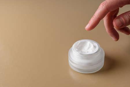 Glass skin cream jar or tube on brown background Standard-Bild