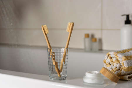 Two bamboo toothbrush in bathroom with towel, body cream and flowing water