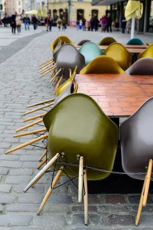 Chairs stacked in a closed street restaurant terrace Standard-Bild