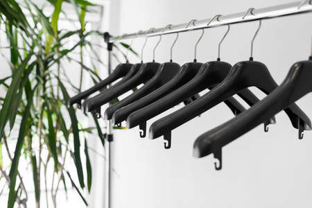 Plastic empty clothes hangers on metallic rail with home palm tree on back
