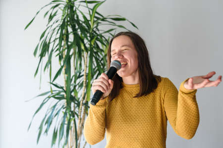 Woman singing with microphone at home with expression