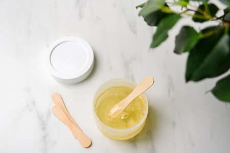 Plastic container with sugarwax and wooden spatulas on marble. Hair removing, epilation