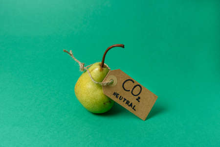 Pear with carbon emission label made from recycled paper on green