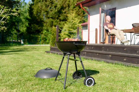 Man preparing grill bbq meat on home backyard at sunny summer day