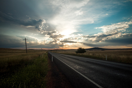 Road stretching into the horizon across vast grassy plains with spectacular sky. Australia