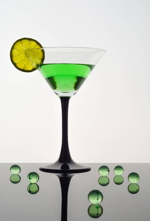 A martini glass with a green drink and a slice of lime on a white background stands on a black glossy surface, next to it are green transparent balls, backlight. Vertical orientation