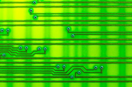 Circuit board as an abstract background, shot with backlight on the lumen. Yellow-green shades, electrically conductive circuits are arranged horizontally. Stockfoto