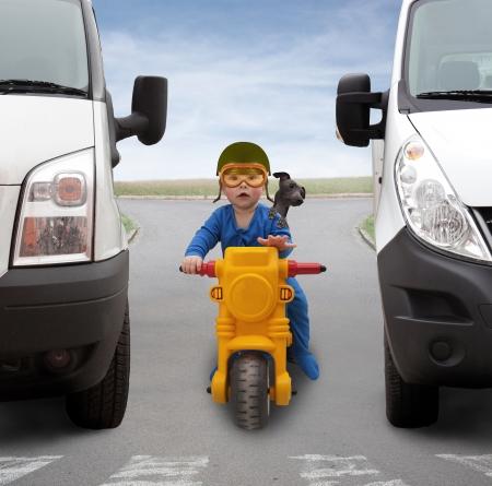 casco de moto: Peque�o ni�o en una moto entre dos coches