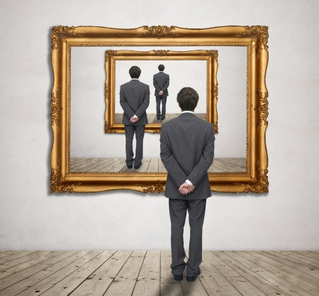 Image of businessman standing in front of a gold frame with his figure Stock Photo