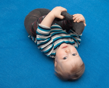 felicity: Small child lying on the blue carpet