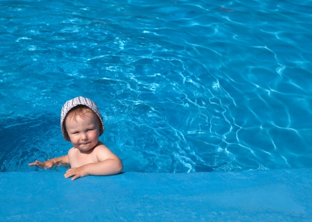 Small baby in swimming pool on holiday