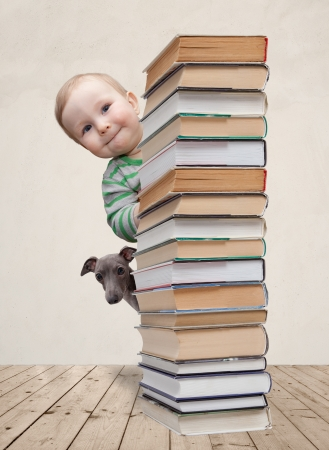 Baby and dog looking behind the column of books