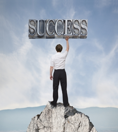 output:  Businessman who climbed the rock and holding in his hand the word success