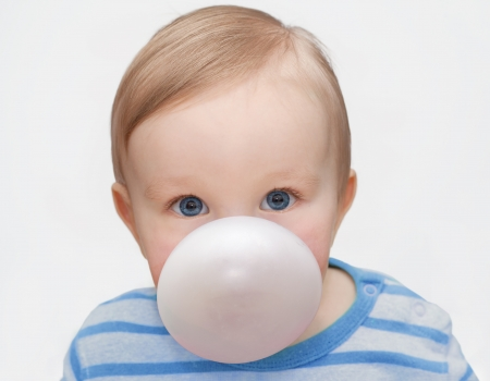 masticate: little boy makes a bubble from chewing gum Stock Photo