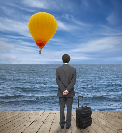 man with a suitcase observes balloon Stock Photo