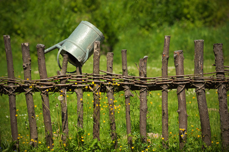old rural fence and watering can photo