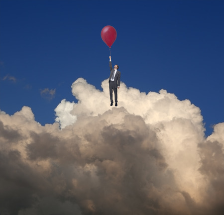 impasse: Businessman using a balloon flying in the clouds