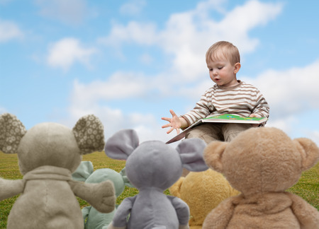 little boy reading a book plush teddy bears Stock Photo