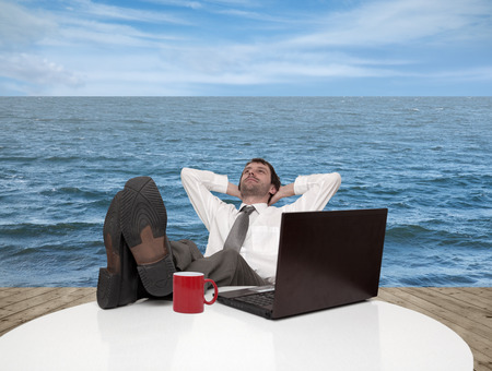 Young businessman relaxes on a pier by the sea Stock Photo