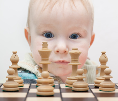 little boy staring at the chess pieces