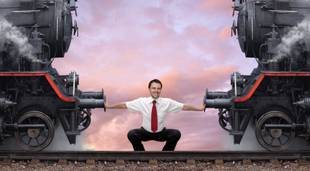 steam locomotives: Young businessman pushes apart two steam locomotives