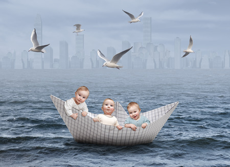 Three boys in a paper boat on the sea Stock Photo