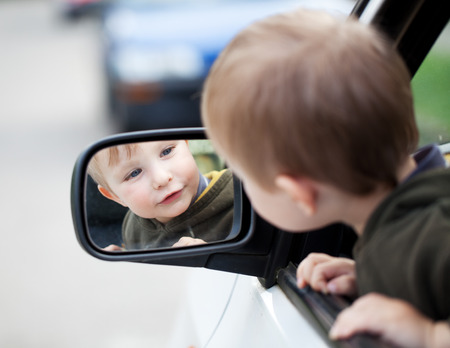 Small child looking to outside mirror Stock Photo