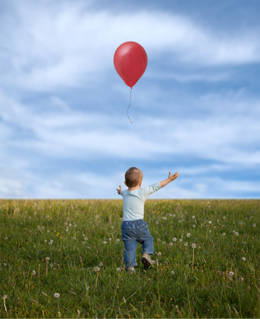 little boy in the spring  meadow and red balloon Stock Photo
