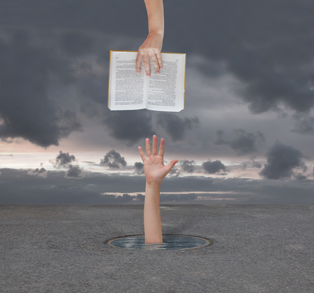hand gives the book a man who is drowning Stock Photo