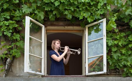 ventana abierta: joven tocando la trompeta en la ventana abierta Foto de archivo