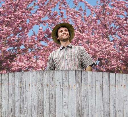 firry: smiling young gardener with straw hat on his head in the garden Stock Photo