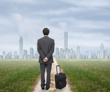 new path: young businessman with his luggage goes to the big city