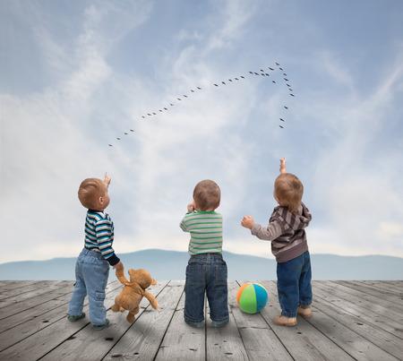 kleine kinderen kijken naar een zwerm vogels Stockfoto