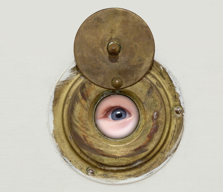 peephole: blue eye looking through the peephole door Stock Photo
