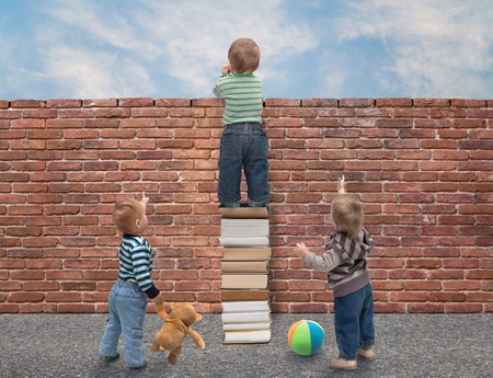 children perceive behind a wall of knowledge Stock Photo