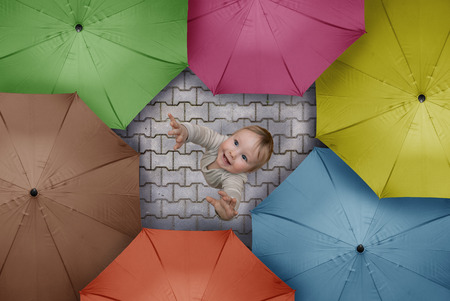 felicity: child in rain and a crowd of colored umbrellas
