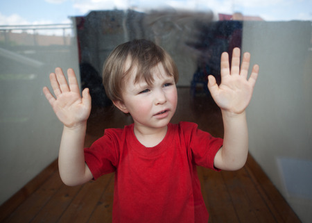 interdiction: triste petit garçon regardant par la fenêtre