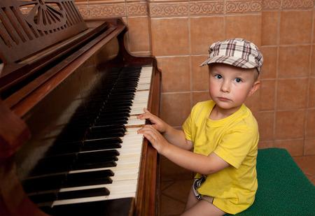 ojos azules: Pequeño músico toca el piano Foto de archivo