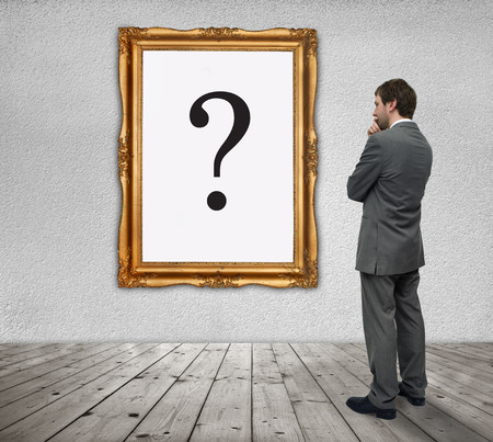 Young Businessman watching the question mark in a gold frame Stock Photo