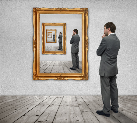 Young businessman looks at himself in the mirror