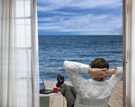 Businessman relaxing on the terrace by the sea Stock Photo - 64055713