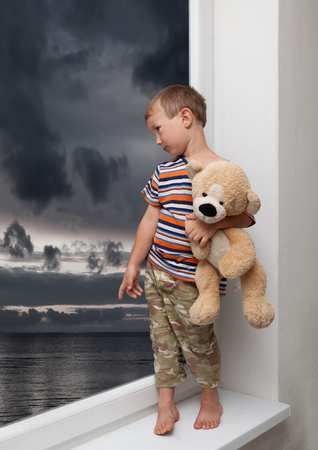 child with a teddy bear looking out the window