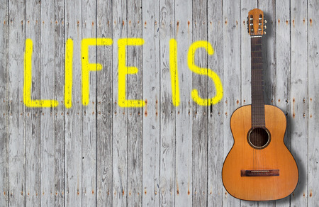 hite sign with life on a wooden fence and a guitar