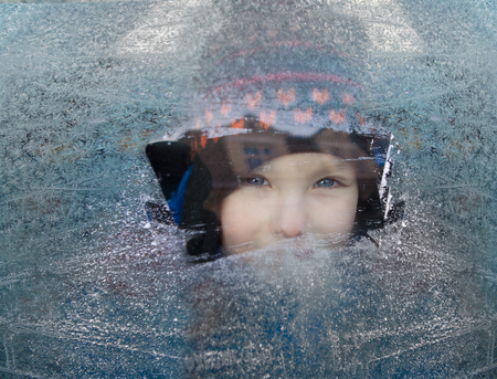 small child looks through a frosted window Stock Photo