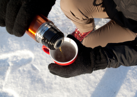tourist pours coffee from a thermos on frost