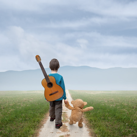 little boy with a guitar and a teddy goes country