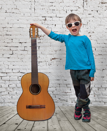 Little boy with glasses and a guitar